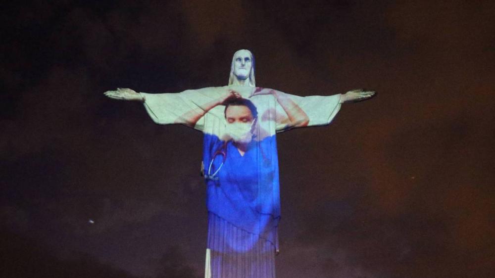 De jaleco, Cristo Redentor homenageia profissionais da saúde